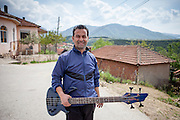 Portrait of a Roma musician with his bass guitar in the Roma part of the city of Vinica in Macedonia, during  the European Immunization Week.