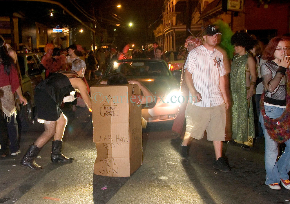 October 31, 2005. New Orleans, Louisiana. <br /> Halloween, post Katrina, New Orleans. As the city returns to a strange sense of normalcy and the citizens return, New Orleans once again hosts a Halloween parade and party. A man in a refrigerator box holds up traffic on Frenchman Street. <br /> Photo; ©Charlie Varley/varleypix.com