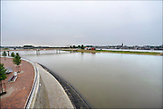 Nederland, Nijmegen, 12-6-2016Nijmegen dingt mee naar de European green capital award die gericht is op duurzaamheid en op 22 juni bekend wordt gemaakt. De bijna 4 km. lange nevengeul van de Waal bij Lent. Grootste onderdeel van de vele werken van Rijkswaterstaat om bij hoogwater een betere waterafvoer in de rivier te hebben. Het dorp veurlent komt op een kunstmatig eiland te liggen met twee kleinere bruggen als ontsluiting. Een voetgangersbrug, de steltlopersbrug voor wandelaars naar het recreatiegebied en een andere, de Promenadebrug, voor normaal verkeer met eronder een voetpad . Ruimte voor de rivier, water, waal. In de nieuwe dijk wordt een drempel gebouwd die stapsgewijs water doorlaat en bij hoogwater overloopt. Het gebied wordt een nieuw gebied voor recreatie en watersportThe Netherlands, Nijmegen Measures taken by Nijmegen to give the river Waal, Rhine, more space to flow during highwater and to prevent the risk of flooding. Room for the river. Reducing the level, waterlevel. Large project to create a new paralel gully, an extra flow of water, so the river can drain more water during highwater. Due to climate change and expected rise, increase of the sealevel, the Dutch continue to protect their land from the water. Foto: Flip Franssen