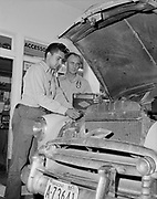 0301-341b Richfield Oil gas station owned by Dick Hornecker (on right) in Wickenburg, Arizona, The two men are under the hood of a car servicing the engine. June 20, 1955