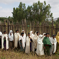 "Women from the village of Mecha watch a demonstration while keeping some distance from hives at the Ambrosia beekeeping demonstration and training centre in Mecha.<br /> <br /> Harvesting honey supplements the income of small farmers in the Ethiopian region of Amhara where there is a long tradition of honey production. However, without the resources to properly invest in production and the continued use of of traditional, low-yielding hives, farmers have not been able to reap proper reward for their labour. <br /> <br /> The formation of the Zembaba Bee Products Development and Marketing Cooperative Union is an attempt to realize the potential of honey production in Amhara and ensure that the benefits reach small producers. <br /> <br /> By providing modern, high-yield hives, protective equipment and training to beekeepers, the Cooperative Union helps increase production and secure a steady supply of honey for which there is growing demand both in and beyond Ethiopia. The collective processing, marketing and distribution of Zembaba's ""Amar"" honey means that profits stay within the cooperative network of 3,500 beekeepers rather than being passed onto brokers and agents. The Union has signed an agreement with the multinational Ambrosia group to supply honey to the export market. <br /> <br /> Zembaba Bee Products Development and Marketing Cooperative Union also provides credit to individual members and trains carpenters in the production of modern hives. <br /> <br /> Photo: Tom Pietrasik<br /> Mecha, Amhara. Ethiopia<br /> November 17th 2010"