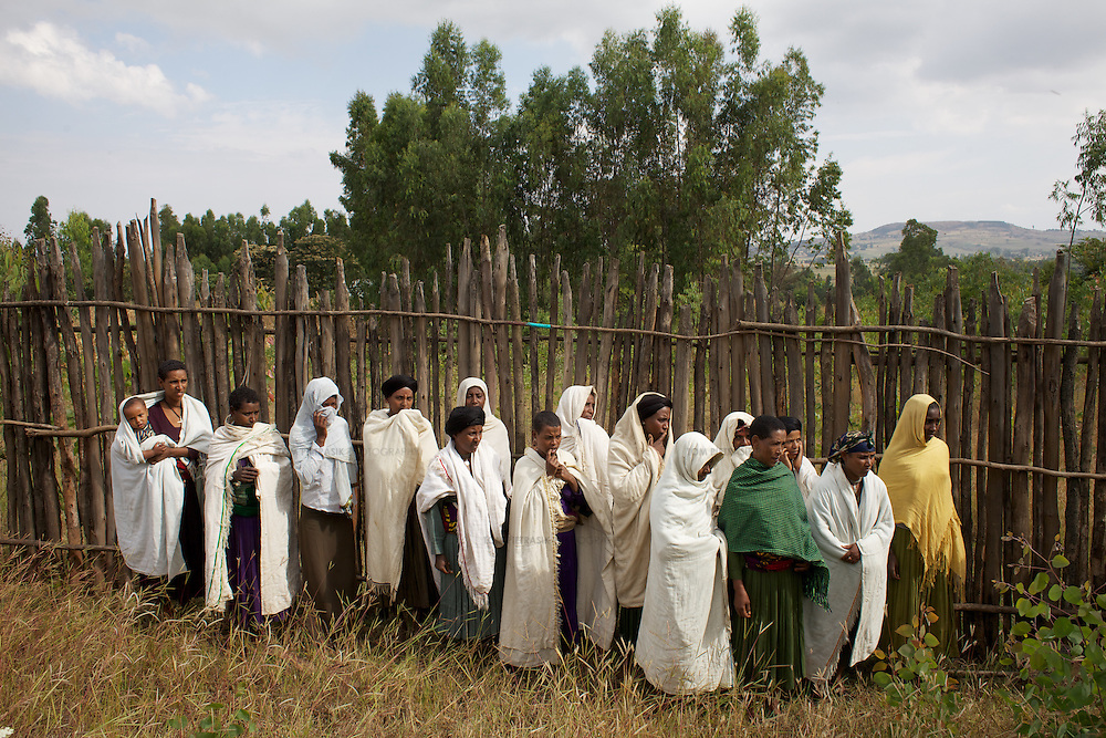 """Women from the village of Mecha watch a demonstration while keeping some distance from hives at the Ambrosia beekeeping demonstration and training centre in Mecha.<br /> <br /> Harvesting honey supplements the income of small farmers in the Ethiopian region of Amhara where there is a long tradition of honey production. However, without the resources to properly invest in production and the continued use of of traditional, low-yielding hives, farmers have not been able to reap proper reward for their labour. <br /> <br /> The formation of the Zembaba Bee Products Development and Marketing Cooperative Union is an attempt to realize the potential of honey production in Amhara and ensure that the benefits reach small producers. <br /> <br /> By providing modern, high-yield hives, protective equipment and training to beekeepers, the Cooperative Union helps increase production and secure a steady supply of honey for which there is growing demand both in and beyond Ethiopia. The collective processing, marketing and distribution of Zembaba's """"Amar"""" honey means that profits stay within the cooperative network of 3,500 beekeepers rather than being passed onto brokers and agents. The Union has signed an agreement with the multinational Ambrosia group to supply honey to the export market. <br /> <br /> Zembaba Bee Products Development and Marketing Cooperative Union also provides credit to individual members and trains carpenters in the production of modern hives. <br /> <br /> Photo: Tom Pietrasik<br /> Mecha, Amhara. Ethiopia<br /> November 17th 2010"""