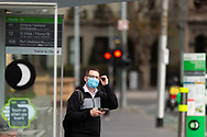 A man wearing a facemask waits for a tram at a tram stop opposite Parliament House during COVID-19. A further 238 Coronavirus cases have been discovered overnight, bringing Victoria's active cases to over 2000, speculation is rising that almost all of Victoria's current cases stem from the Andrews Government botched hotel quarantine scheme as well as the Black Lives Matter protest.  Premier Daniel Andrews warns that Victoria may go to Stage 4 lockdown if these high numbers continue. (Photo be Dave Hewison/ Speed Media)