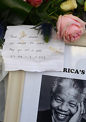 © Licensed to London News Pictures.06/12/2013. London, UK. A message left 'Thank you Madiba (clan name of Mandela), you changed the World. May you rest in peace' at the statue of Nelson Mandela in Parliament Square, London to pay tribute to late former South African president Nelson Mandela following his death in Johannesburg.Photo credit : Peter Kollanyi/LNP