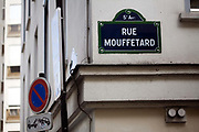 A street sign for Rue Mouffetard. <br /> Rue Mouffetard is in the Fifth (cinquieme) arrondisement and the street is one of the oldest in Paris. A Roman road, it originally ran from the Roman Rive Gauche city all the way to Italy. Today, the market is famous for it's quality fresh produce and artisanal food shops.