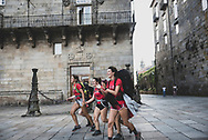 A group of teenagers run as they enter Obradoiro Square, the end-point of their walk on the Camino de Santiago in Santiago de Compostela, Spain. (July 14, 2018)<br />
