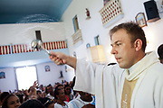 Priest blessing the congrigation with Holy water. Often the lines between Candomble and Catholicism are blurred. This is especially true with the Sao Lazaro event in late January in Salvador, Bahia, Brazil, the city which is known as the home of Candomble. Sao Lazaro represents healing and the sick.