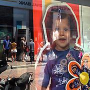 Cash machine reflected in the window of a photoshop. #crete #greece #reflection #child #window #photoshop #hellas #portrait #street #chania #window #bank