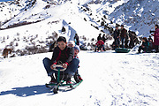 A young family enjoy a toboggan ride at the base of Chimgan ski resort on 28th February 2014 in Uzbekistan. Chimgan is 90kms east of the capital Tashkent, and a popular weekend destination year round.