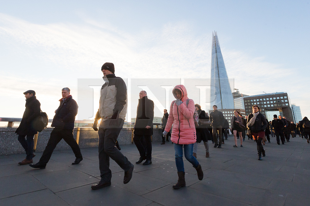 © Licensed to London News Pictures. 30/11/2017. London, UK. Commuters walk to work across London Bridge during cold weather this morning. The capital experienced freezing temperatures last night during one of the coldest night of the year so far.. Photo credit: Vickie Flores/LNP