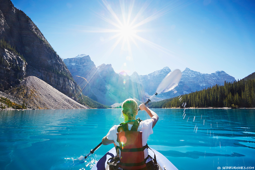 Kayaking across the glacial, blue waters of Moraine Lake in Banff National Park, Canada.