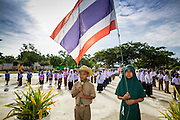 11 JULY 2013 - PATTANI, PATTANI, THAILAND:   Students raise the Thai flag at the Bantaladnadklongkud School in Pattani. There are 108 students at Bantaladnadklongkud School and they are all Muslims. Five of the school's eight teachers are Buddhists.    PHOTO BY JACK KURTZ