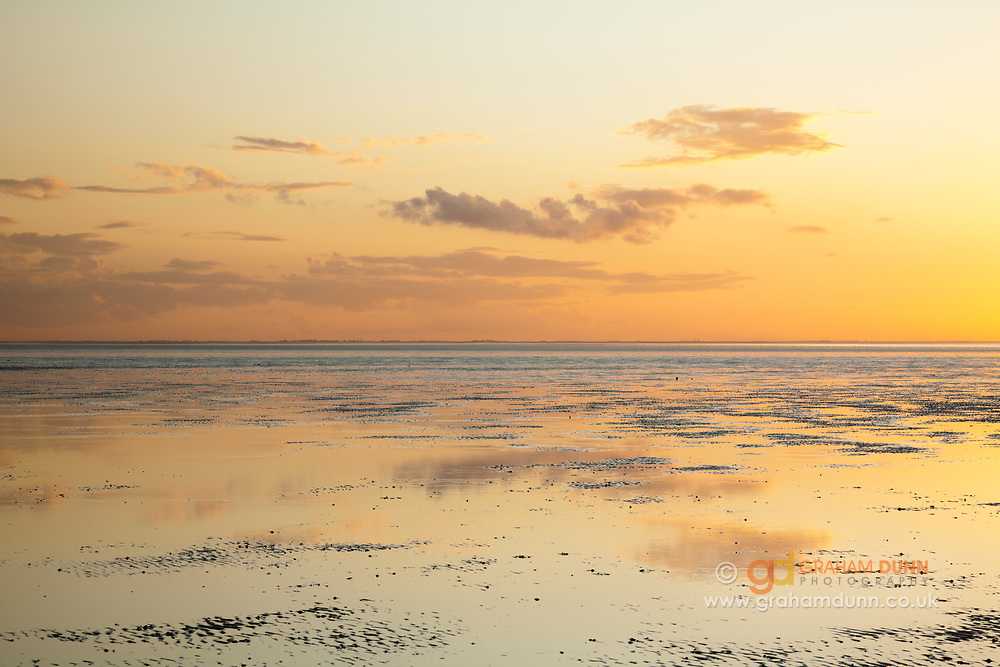 Still low tide waters reflect the evening sky at Stubborn Sand, Heacham. A sunset beach scene in North Norfolk, East Anglia.