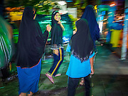 16 JULY 2013 - BANGKOK, THAILAND:   Muslim girls walk home from Jami Ul Khoy Riyah Mosque in the Ban Krua section of Bangkok after celebrating the Iftar meal. Iftar is the Muslim meal that breaks the day long Ramadan fast. Ban Krua is the oldest Muslim section of Bangkok. It was established during the reign of Rama I, the first King of the Chakri dynasty. He enlisted Cham Muslims in what is now Cambodia to fight on the Siamese (Thai) side of war between the Khmers and Siamese. He rewarded their service with a grant of land that is now Ban Krua.      PHOTO BY JACK KURTZ