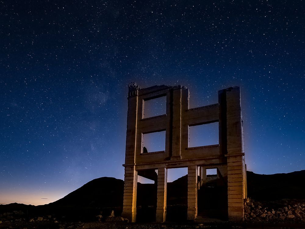 United States, Nevada, Rhyolite ghost town.  Ruins of bank building at night with stars