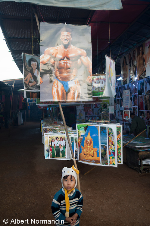 Young boy in front of muscle man poster at Ananda Temple Festival