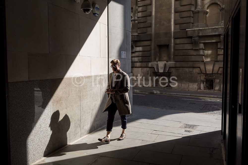 A stylish man walks through shafts of light on Lombard Street in the heart of the capitals financial district, on 19th April, in the City of London, England.