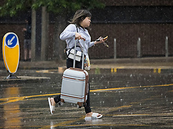 © Licensed to London News Pictures. 07/08/2021. London, UK. A member of the public gets caught in a downpour of rain in Wood Green, North London. Heavy rain is expected to cause flash flooding in parts of the UK. Photo credit: Ben Cawthra/LNP