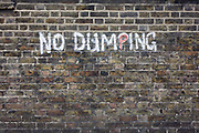 The words 'No Dumping' writing on an urban brick wall in the south London borough of Lewisham, SE5. Painted by hand on to London stock bricks dating perhaps, to the late-Victorian or early 20th century period, we see the writing asking local residents and business owners not to fly-tip in this unauthorised location. Councils like Lewisham will prosecute those found to be dumping waste and litter. Amusingly, we also notice that the letter P has been empasised with the use of red.