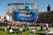 March 28th 2012. Demonstration organised by NUT (National Union of Teachers) to protest against changes to pensions and retirement age. A giant inflatable vice squeezing a pound is anchored outside Parliament.