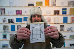 © licensed to London News Pictures. London, UK 23/03/2013. Andrew Stanford buys a postcard sized artwork made by Christo from the Royal College of Art's Secret Postcard Sale. 2,700 postcard sized works of art, which have been donated by artists, designers, illustrators and film-makers including Paula Rego, Julian Opie and David Bailey, sold for £45 at the Royal College of Art in Battersea on Saturday 23 March 2013. Photo credit: Tolga Akmen/LNP