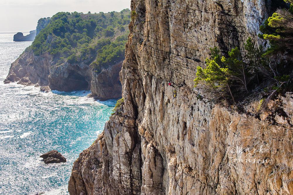2 men rock climbing on a high sea cliff at Punta Ventosa, Montgo, L'escala, Catalonia, Spain