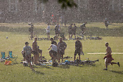 After an afternoon of sunshine and warm temperatures during the continuing UK Coronavirus lockdown, a sudden and torrential downpour of rain catches park users by surprise, in Ruskin Park, a public green space in Lambeth, on 14th June 2020, in London, England. The current UK Covid-19 death toll now stands at 41,662, an increase over the last 24 hours of 181, although Prime Minister Boris Johnson is coming under pressure to review the case for a reduction of the 2 metre social distance rule, due to its effect on jobs and wider economy.