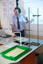 Secondary School Science teacher using whiteboard to explain to students the formula of a kinetic energy experiment on why and how things move; with practical ski jump experiment in the foreground,