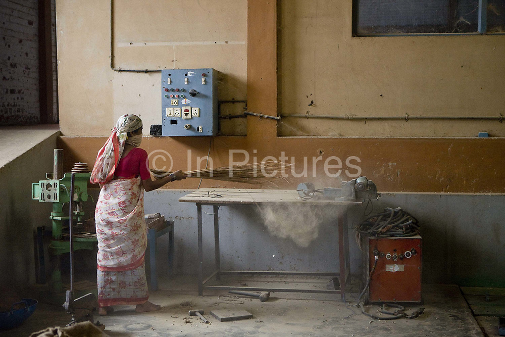 Coffee processing factory, worker sweeping up coffee dust. Coorg or Kadagu is the largest coffee growing region of India, in the state of Karnataka, the inhabitants - the Kodavas have been cultivating crops such as coffee, black pepper and cardamon for many generations.