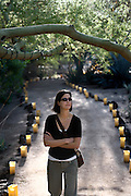 SHOT 12/18/2007 - Margaret Ebeling of Denver, Co. strolls through a luminaria lined path in the Desert Botanical Garden in Phoenix, Az. one afternoon. The Desert Botanical Garden is a 50 acre (20 ha) botanical garden located within Papago Park in Phoenix, Arizona, USA. Founded in 1939, the garden now has more than 21,000 plants, including 139 species which are rare, threatened or endangered. Of special note are the rich collections of agave (176 taxa) and cacti (10,350 plants in 1,350 taxa), especially the Opuntia sub-family. The Desert Botanical Garden has been designated as a Phoenix Point of Pride..(Photo by Marc Piscotty/ © 2007)