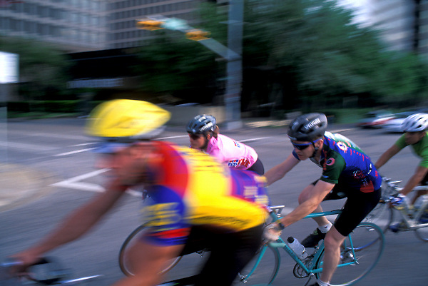 Stock photo of a group of cyclists racing through downtown