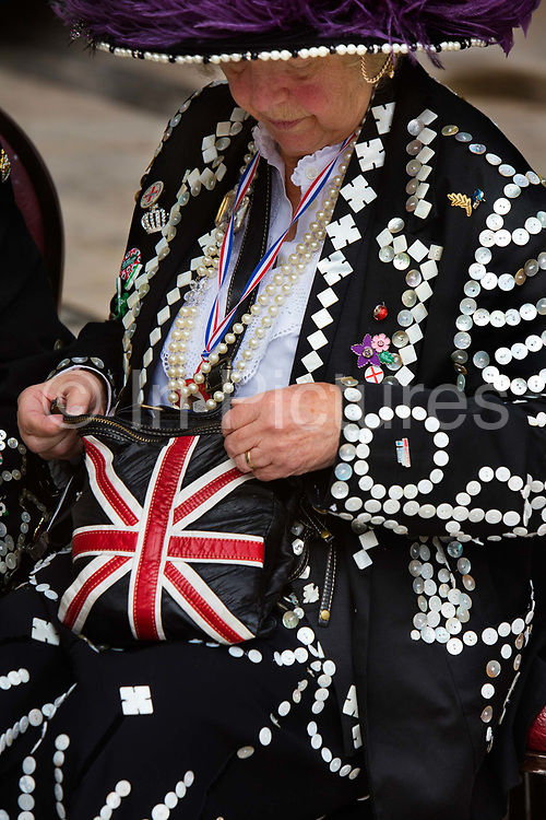 Union Jack handbag at the Pearly Kings and Queens Harvest Festival celebrations at Guildhall Yard. The annual event features early English entertainment including maypole dancing, Morris dancers and a marching band. The Chelsea pensioners & all the mayors of London take part in this traditional London event.<br /> The London tradition of the Pearly Kings and Queens began in 1875, by Henry Croft. Inspired by the local Costermongers, a close-knit group of market traders who looked after one another and were recognisable by buttons sewed onto their garments, Henry went out on the streets to collect money for charity, wearing a suit covered in pearl buttons to attract attention. When demand for his help became too much, Henry asked the Costermongers for assistance, many of whom became the first Pearly Families. Today, around 30 Pearly Families continue the tradition to raise money for various charities.