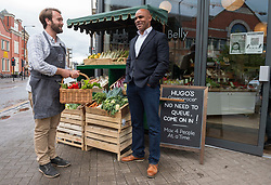 """© Licensed to London News Pictures; 24/05/2021; Bristol, UK. Bristol's elected Mayor MARVIN REES (right), with GARY DERHAM (left) owner of The Bristol Loaf on Bedminster Parade. The mayor met shoppers and traders in Bedminster to launch """"Where's it To?"""", a new high street support campaign by Bristol City Council. Where's it to? is an invitation to Bristolians to explore their local high streets, shop local and get to know the traders behind the businesses. 15 high streets across the city will be profiled, highlighting numerous traders on each street, which span from stores passed through generations of a family, through to brand new openings inspired by the covid coronavirus pandemic. The phrase """"Where's it to?"""" is what Bristolians traditionally say meaning 'where is that?' and  was selected as the name of the campaign to reflect the city's language and in collaboration with a huge range of traders from across the 15 high streets. Photo credit: Simon Chapman/LNP."""