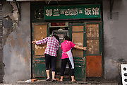 Two women close up their traditional shop along a hutong in Beijing, China