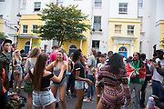 Crowds dancing to music at I Spy The People sound system on Colville Gardens. Notting Hill Carnival in West London. A celebration of West Indian / Caribbean culture and Europe's largest street party, festival and parade. Revellers come in their hundreds of thousands to have fun, dance, drink and let go in the brilliant atmosphere. It is led by members of the West Indian / Caribbrean community, particularly the Trinidadian and Tobagonian British population, many of whom have lived in the area since the 1950s. The carnival has attracted up to 2 million people in the past and centres around a parade of floats, dancers and sound systems.