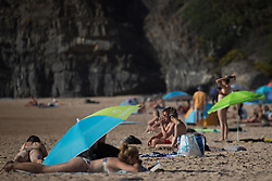 © Licensed to London News Pictures.  11/10/2021. Faro, Portugal. Sunseekers enjoy a warm and sunny weather along the coast in Amado Beach, Algarve, Portugal as  the UK's traffic light system has been scrapped last Monday, with locations categorised as either on the red list or not. NHS COVID Pass holders, who do not also have an EU digital COVID certificate, must take a COVID-19 test to enter Portugal. Photo credit: Marcin Nowak/LNP
