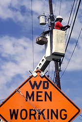 Stock photo of a woman working on a power line with an amended caution sign