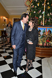 JOAN COLLINS and PERCY GIBSON at the Claridge's Christmas Tree By Dolce & Gabbana Launch Party held at Claridge's, Brook Street, London on 26th November 2013.