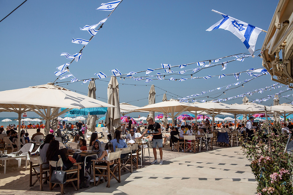People sit at a restaurant during Independence Day celebrations in Tel-Aviv, Israel April 15, 2021. People gathered in their masses at Tel-Aviv's shore line as the Jewish state celebrates 73 years to it's establishment. As vast percentage of the population are vaccinated, celebrations were able to take place in a some what ordinary manner.Starting Sunday April 18, 2021, it will no longer be mandatory to wear a protective mask in open spaces throughout the country.