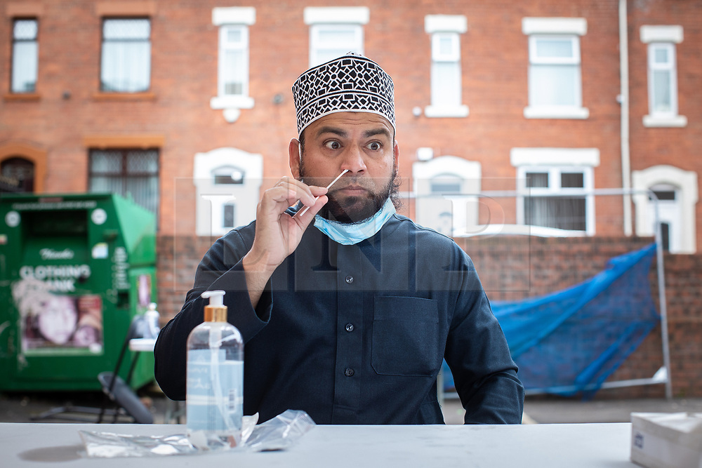 © Licensed to London News Pictures . 21/08/2020. Oldham , UK . Al-Madina Jamia Masjid Mosque Imam SAQIB QADRI (45) takes a Coronavirus test at a temporary testing station underneath a gazebo in the mosque car park . Stricter measures are being imposed in Oldham in order to stem the number of residents being infected by Coronavirus and Muslim community leaders are taking steps to encourage measures to reduce the spread . Photo credit : Joel Goodman/LNP