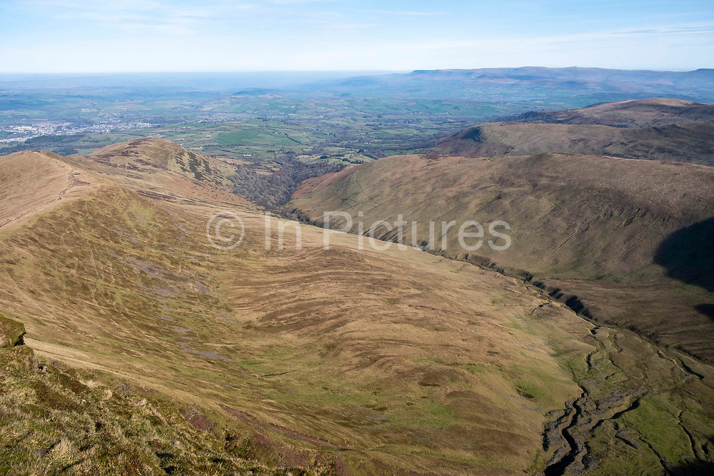 Dramatic landscape view from the summit of Pen Y Fan down the steep incline across the valleys of Brecon Beacons National Park, Wales, Powys, United Kingdom.  Pen Y Fan is the highest point in the Brecon Beacons hill and mountain range in South Wales. The National Park was established in 1957 due to the spectacular landscape which is rich in natural beauty and is run by the National Trust.