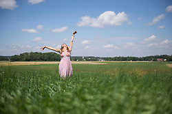 Happy woman enjoying with arms raised on meadow in the countryside, Bavaria, Germany