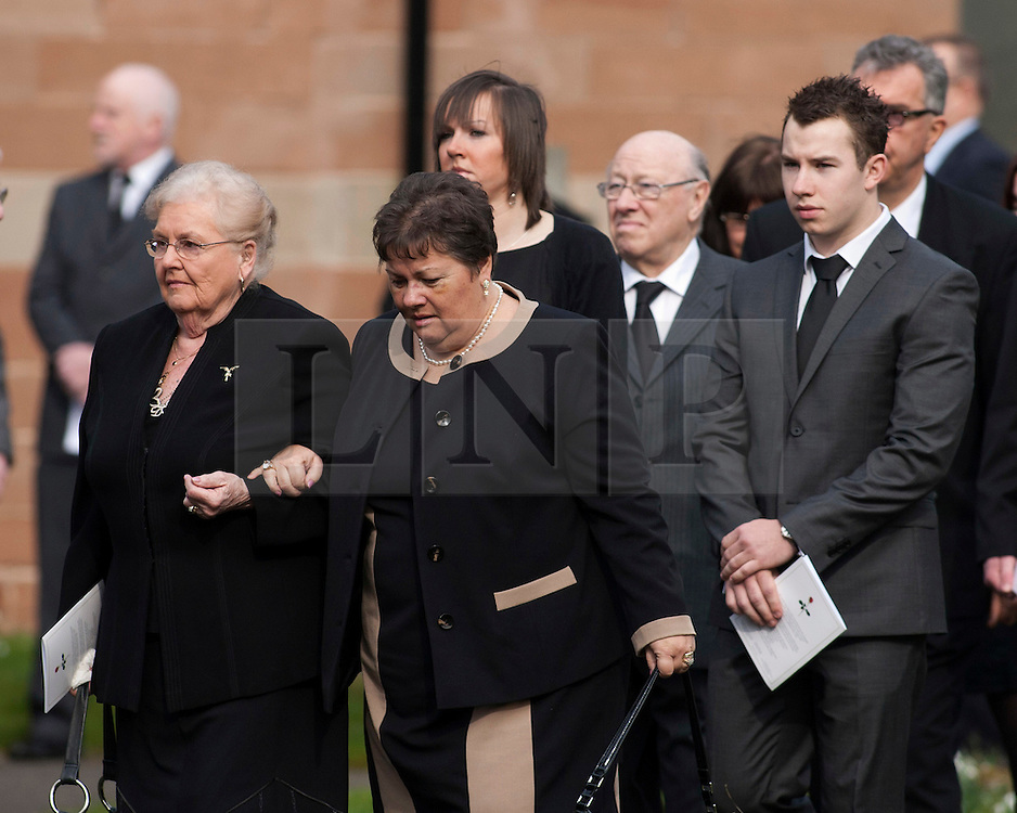 © Licensed to London News Pictures.2/3/2012. Alvechurch, Worcestershire. The funeral of teacher Peter Rippington took place earlier today in the village where he taught. The 59-year-old died of multiple injuries at the scene of the crash on the A26 in France on February 19. Pictured, Sharon Rippington (centre,dark hair) follows the coffin out of the church. Photo credit : Dave Warren/LNP