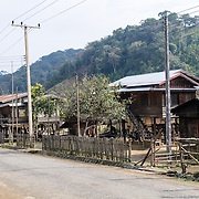 A village in the Plain of Jars in northeastern Laos. With its wooden house frames and corrugated iron roofs, as well as electricity cables, this village, which specializes in weaving, is fairly wealthy by rural Lao standards.