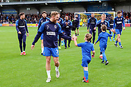 AFC Wimbledon midfielder Scott Wagstaff (7) slapping hands with Mascot during the EFL Sky Bet League 1 match between AFC Wimbledon and Lincoln City at the Cherry Red Records Stadium, Kingston, England on 2 November 2019.