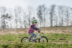 Little girl riding bicycle on field
