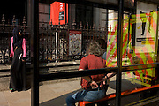 Reflections of londoners and the reflected rear of an NHS London ambulance stopped near a bus shelter.