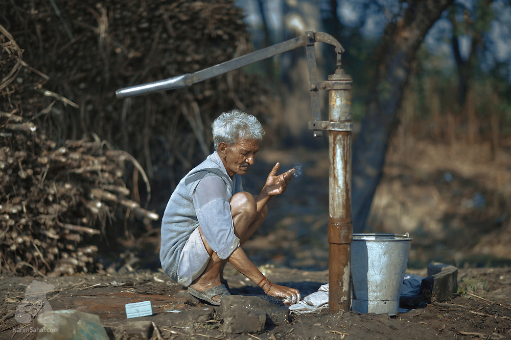 Smoking with one hand and washing his clothes with the other, a man crouching at a village's water well pump in rural Punjab, India, proves that men can also multitask.