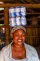 Woman balancing beer cans on her head, Kwara Camp, Okavango Delta, Botswana.