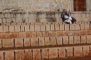 A man reads the newspaper along the steps of the Santo Domingo de Guzmán Church in Oaxaca, Mexico.